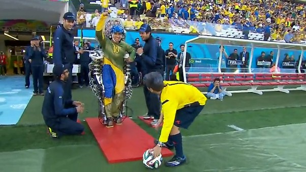 paraplegic with a mind controlled exo-skeleton taking the first kick of the world cup