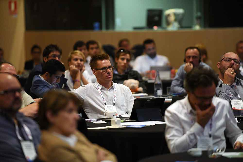 IAAPA EAS euro attractions show conference meeting man sat in white shirt with glasses in a group