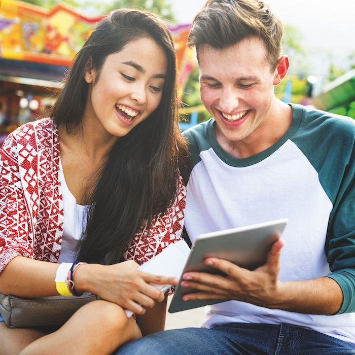 couple look at ipad for theme park ticketing sollutions