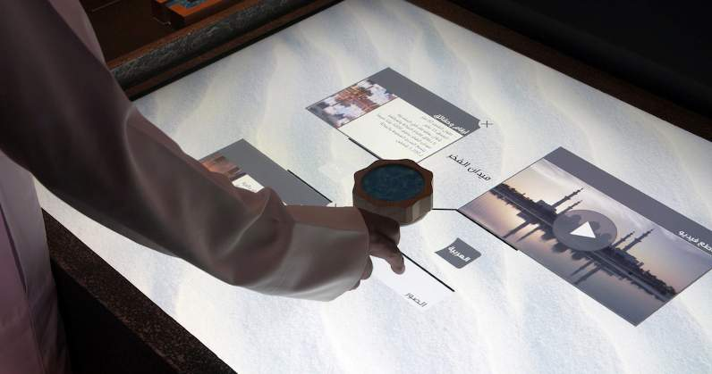 hand operating interactive medai table at Thinkwell Group's new visitor centre experience for Wahat Al Karama Memorial, Abu Dhabi