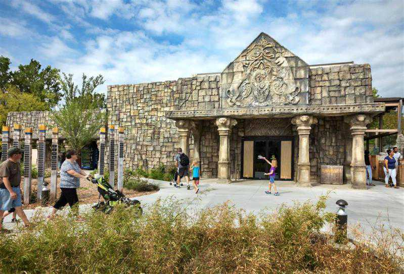 woman pushes pram outside temple at PGAV-designed Lost Kingdom exhibit opens at Tulsa Zoo