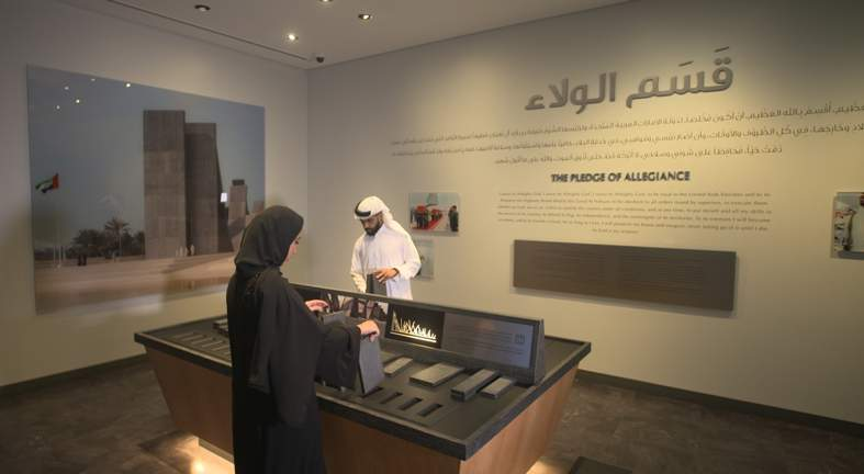 man and woman in Arab clothing interact with Thinkwell Group's new visitor centre experience for Wahat Al Karama Memorial, Abu Dhabi