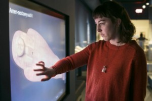 woman places hand on interactive 3D screen showing egyptian mummy at saint louis art museum