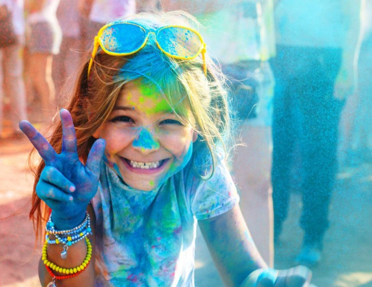 girl sprayed with paint at colour fun run pgav destinations