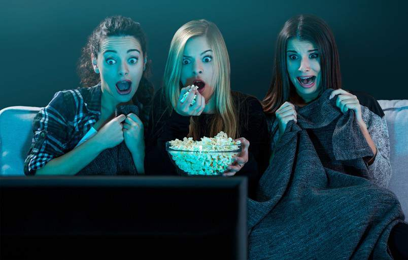 girls eating popcorn and watching horror film