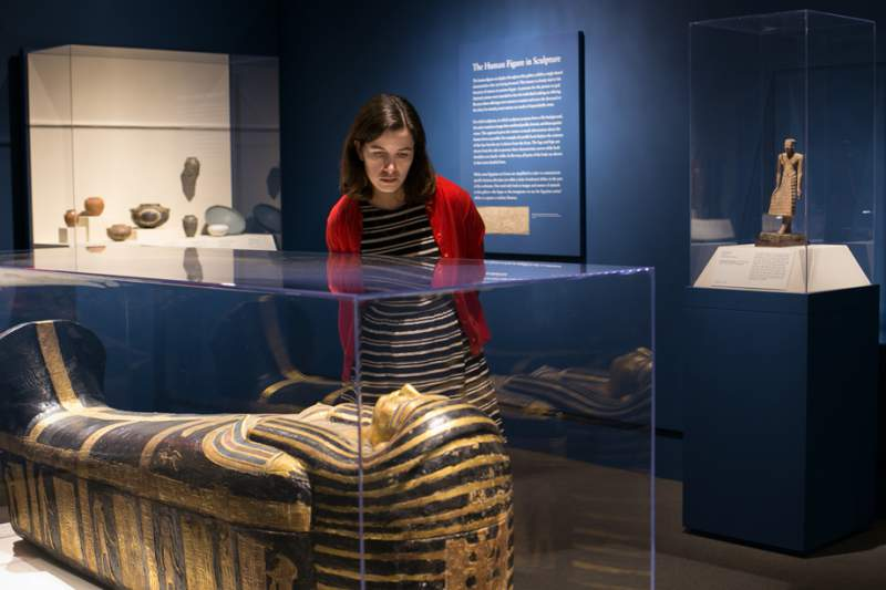 woman views egyptian mummy in case at saint louis art museum