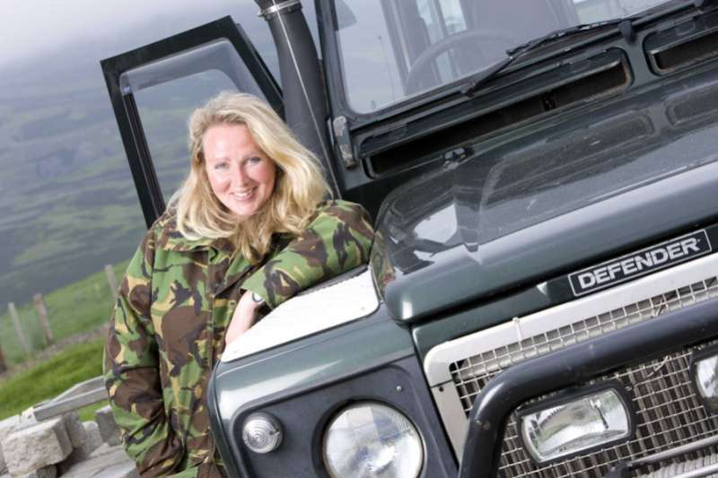 Ghillie Basan standing by Land Rover Defender