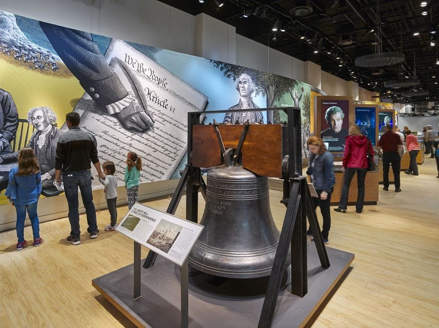 Visitors exploring the exhibit with a bell located in the middle