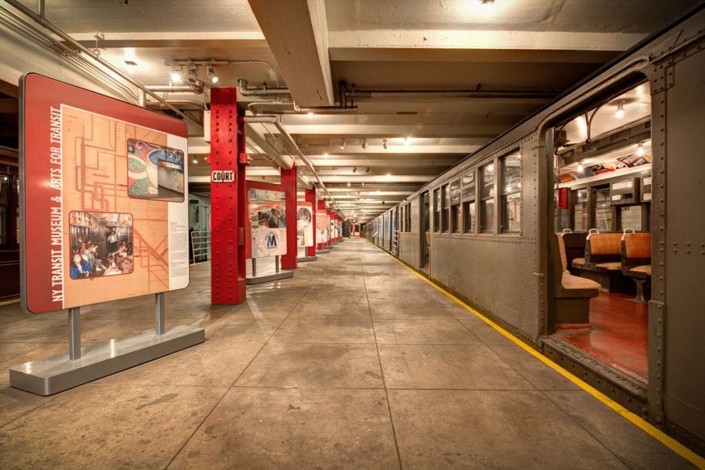 Exhibition on the left side of the platform of the New York Transit Museum, with a train carriage on the right