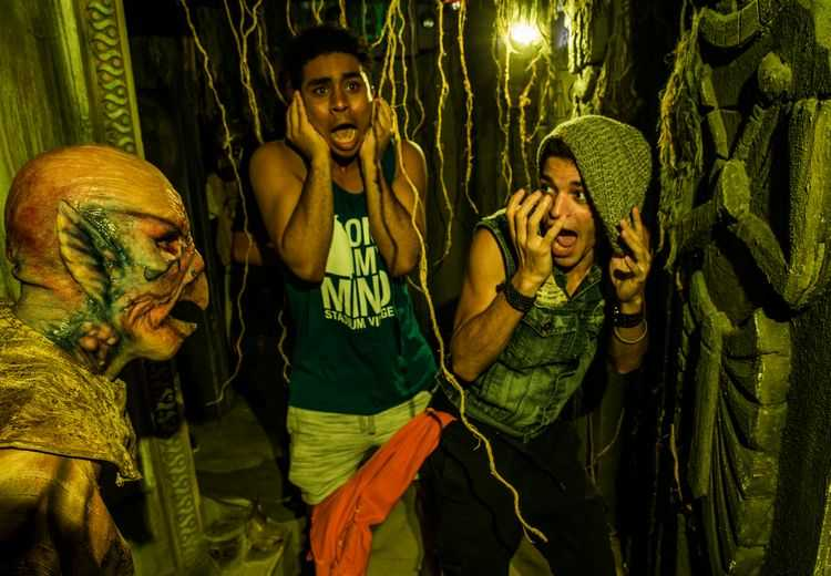 Two guests reacting in fear to scare actor at HHN Halloween Horror Nights