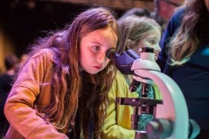 Young girl looking into a microscope at Liverpool Light Night