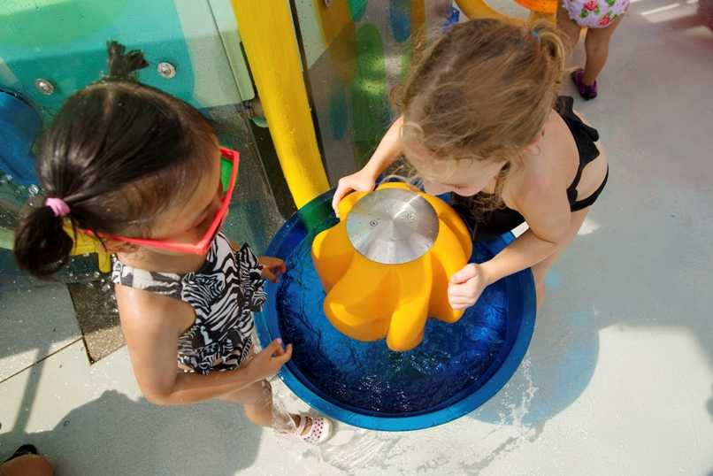two girls play with playnuk aquatic play structure