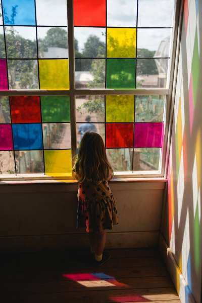 girl looks through stained glass at weehailes at newhailes house