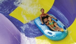 Mother and daughter on a two person raft taking a turn on a circular bowl on the water slide