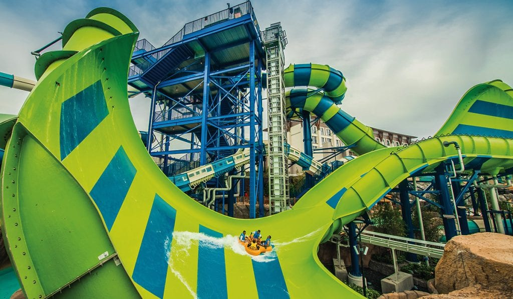Landscape image of a large green water sldie with a large wall. Riders are on a yellow raft about to climb teh wall before descending down the slide.