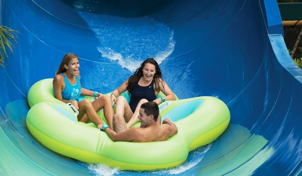 Three riders on a raft sliding down the last part of a water slide