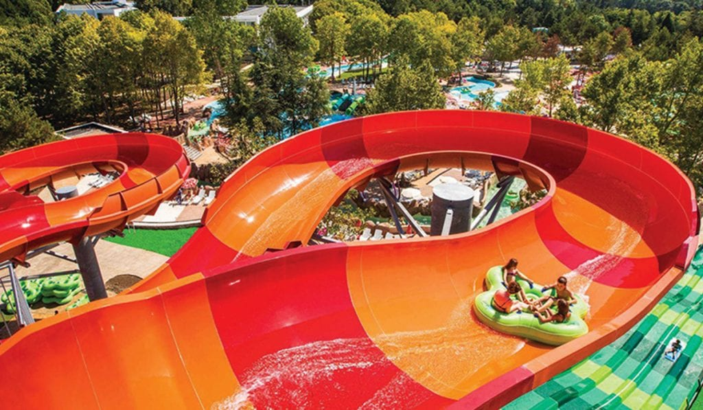 Large four person raft going down a large water slide with quick turns