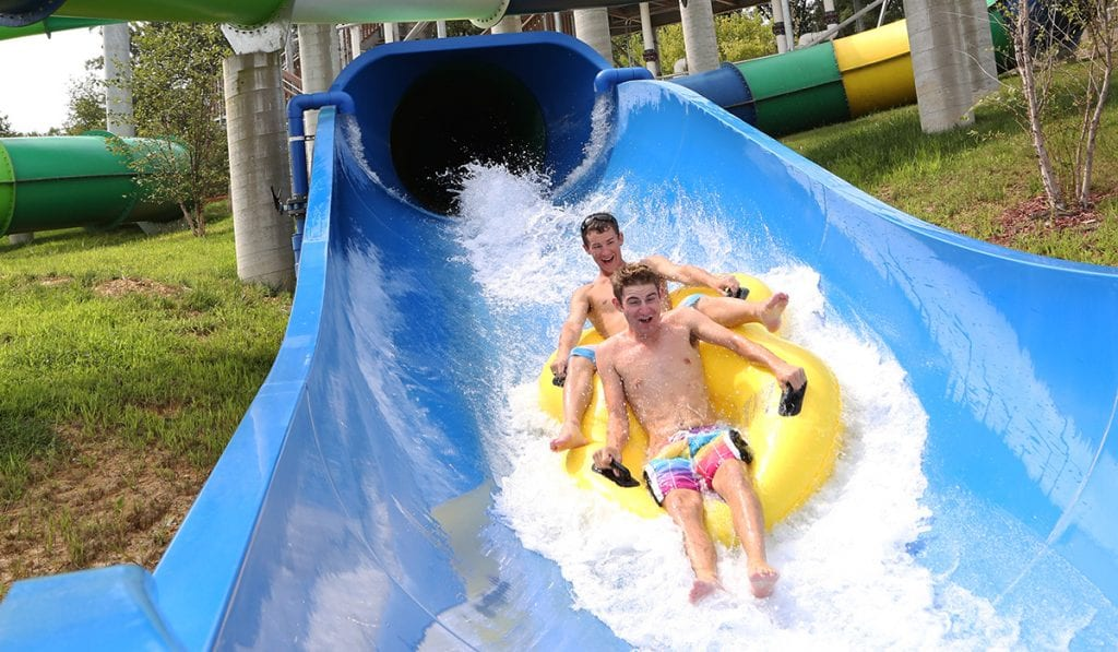 Close-up view of two individuals in a raft going down a blue pipeline coming towards the camera