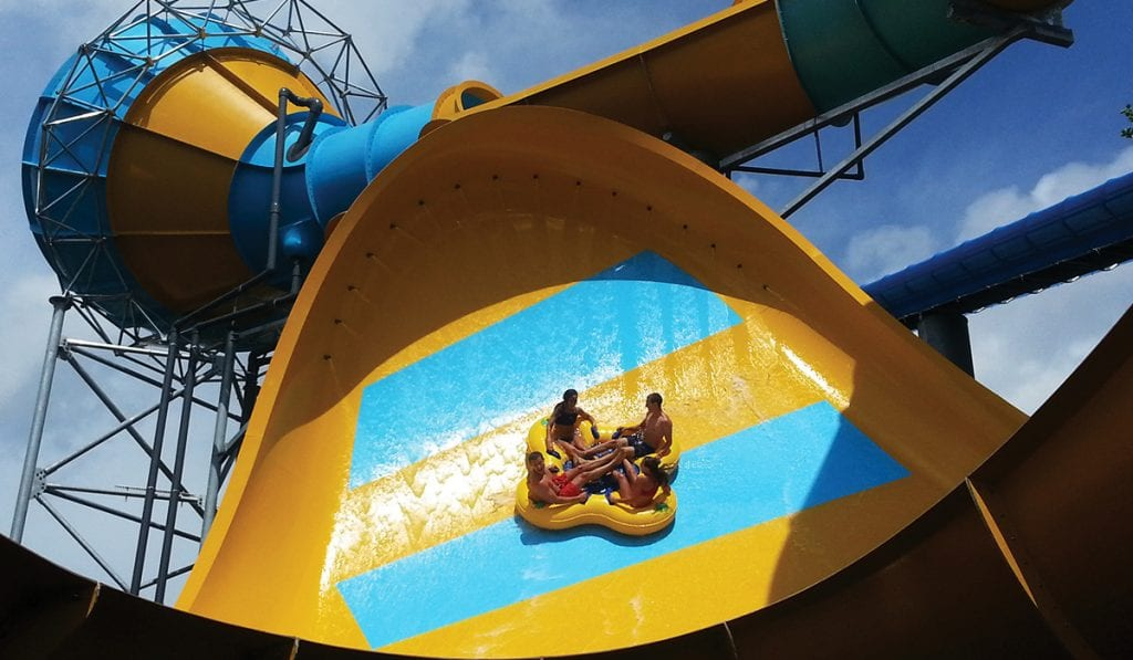 Four individuals on a yellow raft about to enter the peak of a tornado wave