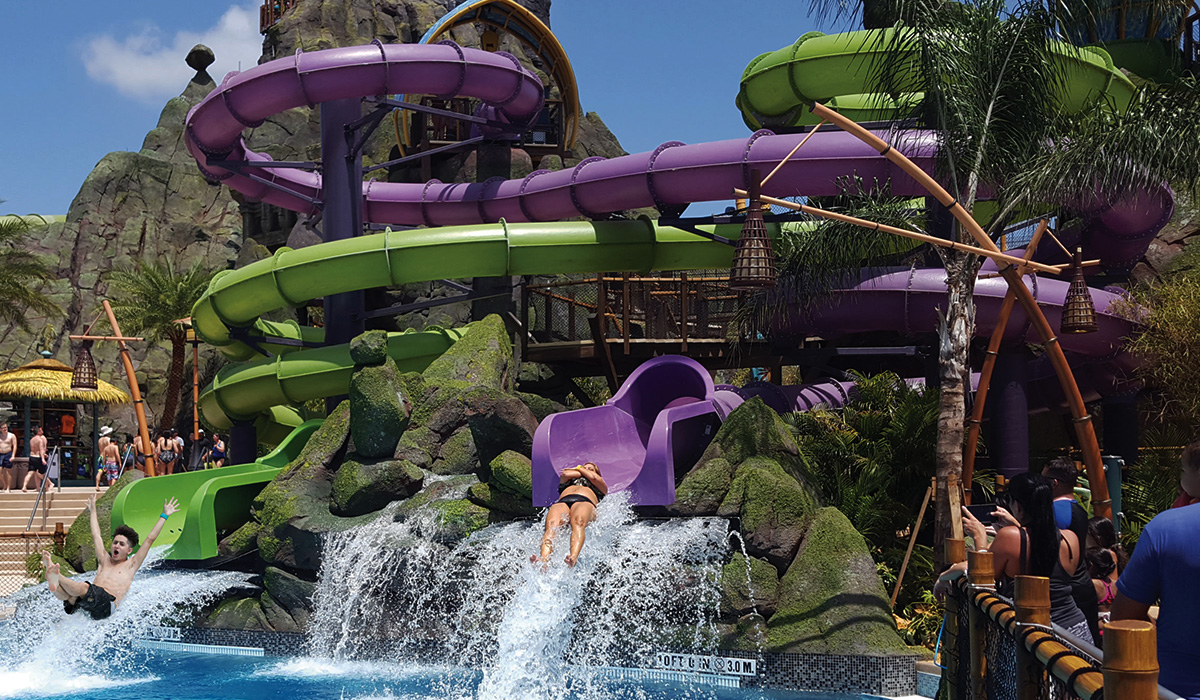Landscape view of two individuals coming out of a twister before they hit the water. Water park theming