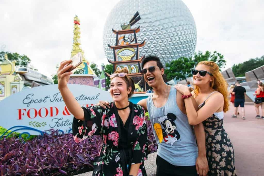 Three guests taking a photo in front of Epcot's International Food and Wine Festival 2018 signage