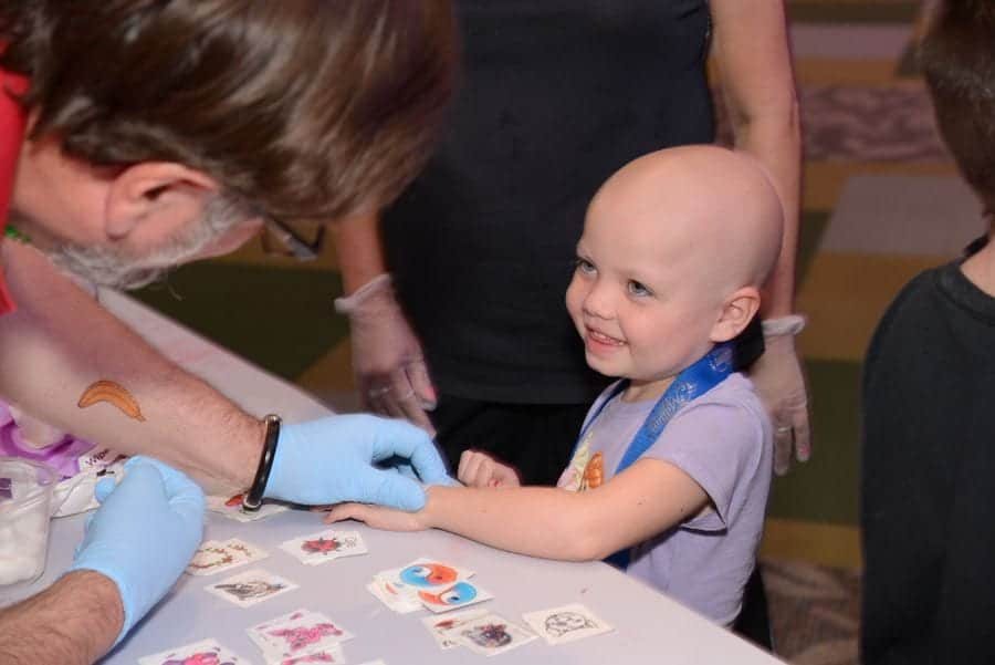 Adult putting a temporary tattoo on a child at Give Kids The World