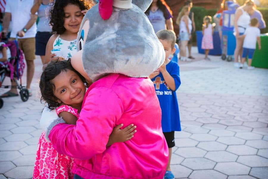 Give Kids The World Mayor Clayton mascot hugging a young girl
