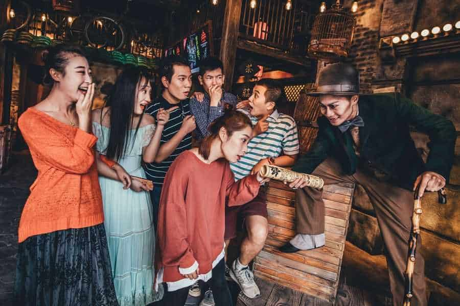 Guests being entertained by actor with walking stick at The Shanghai Dungeon