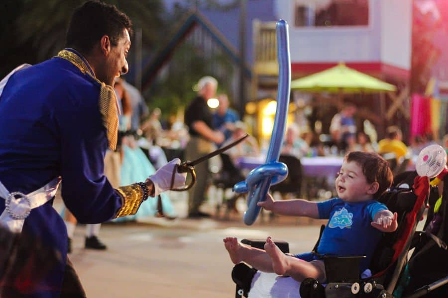 Prince at Give Kids The World interacts with a young boy on wheelchair