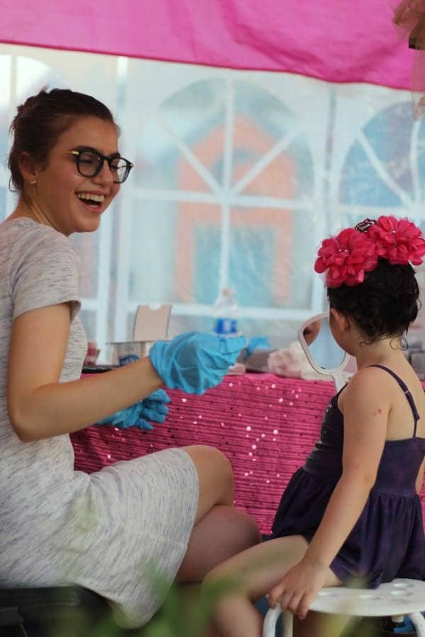 Sami Gayle applying makeup for a young girl's makeover at Give Kids The World