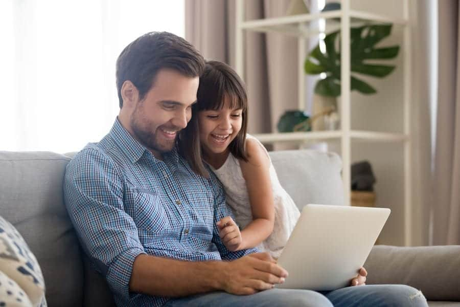 Smiling father and daughter looking at a screen