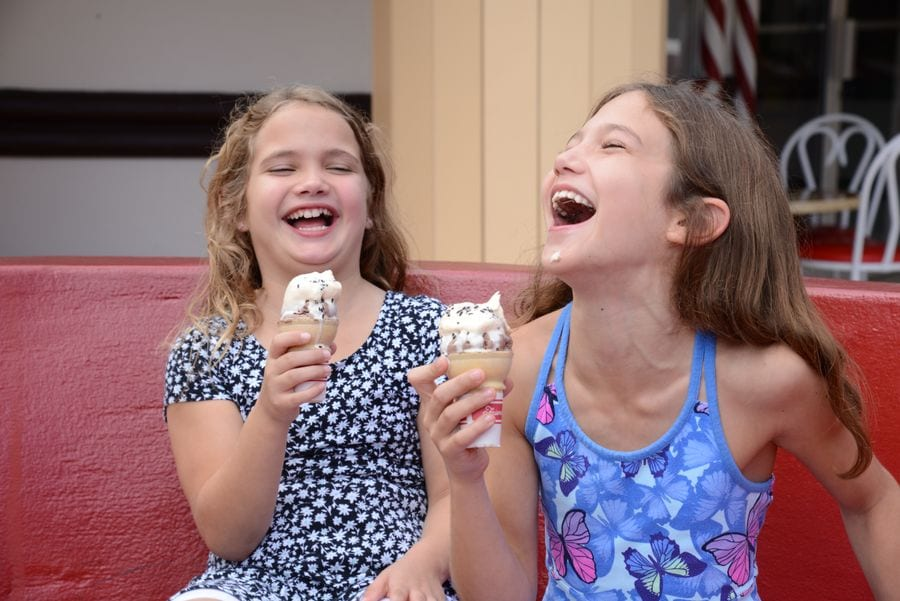 Two young girls laughing and eating ice cream at Give Kids The World