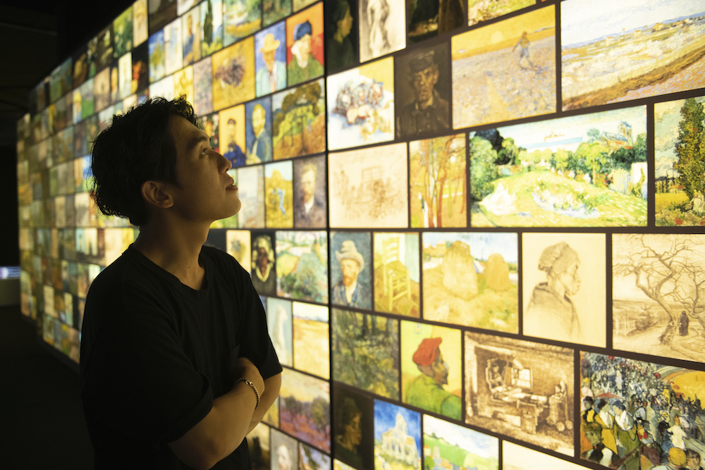woman looking at Vincent van Gogh's paintings at travelling exhibition
