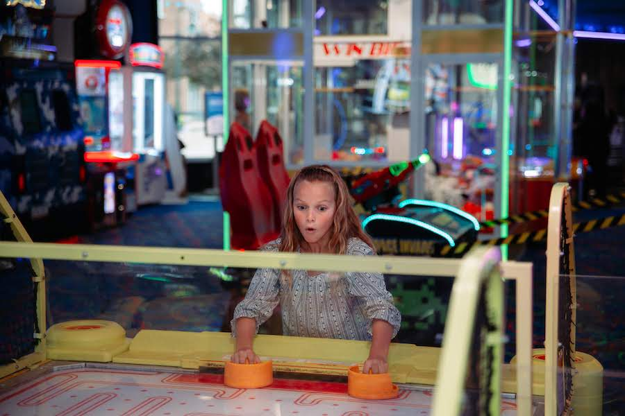 Girl enjoy air hockey at Arcade City by FACE Amusement
