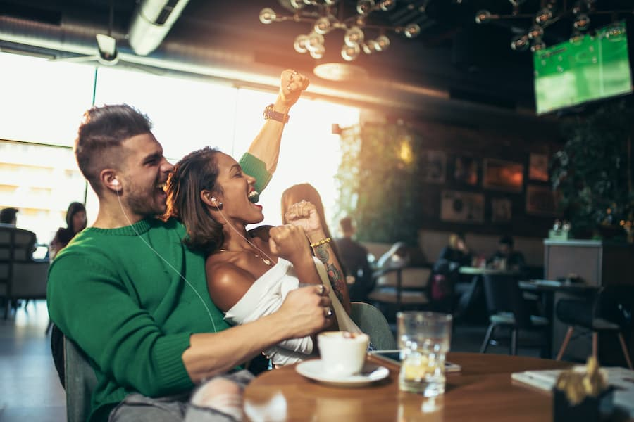 Couple looking happy after their football team score thanks to Listen EVERYWHERE
