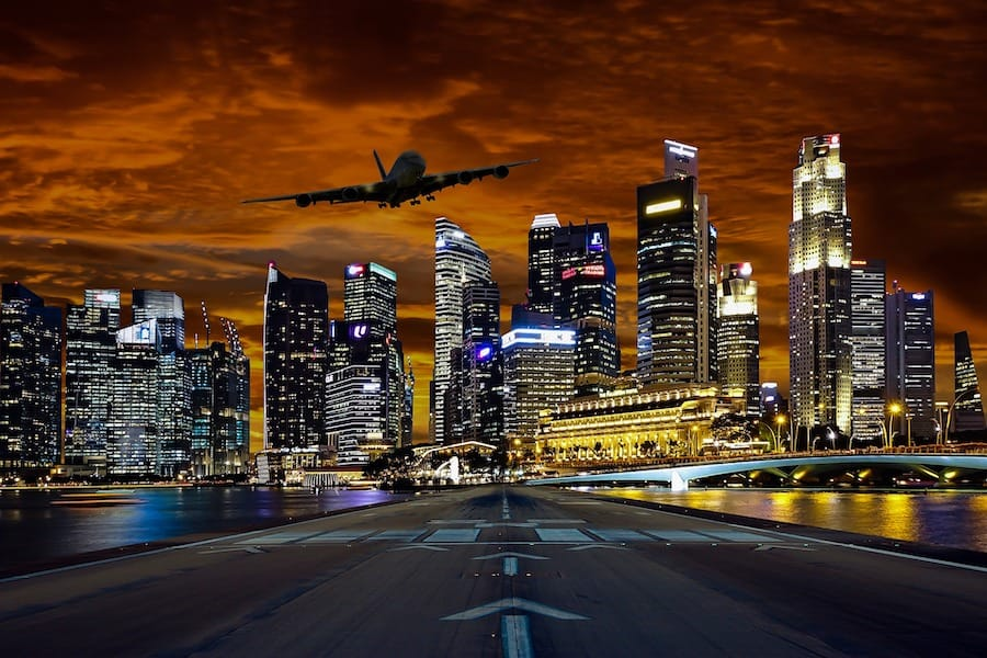 Aeroplane coming in to land over Singapore city at night