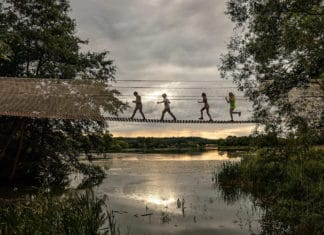children crossing rope bridge over to Skelf Island at Castle Howard at sunset