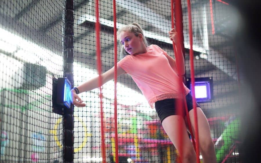 Girl touches wristband to TAG Active touchpoint on ropes course from iplayco showcasing at Amuseument Expo 2020