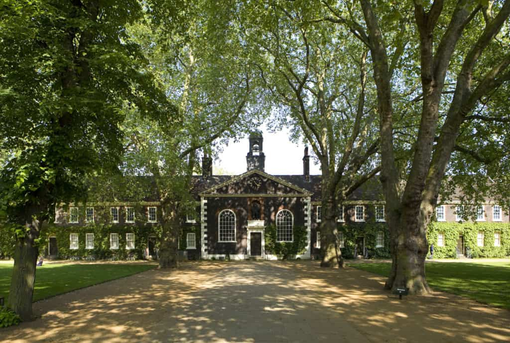 A wide-angle shot of the Museum of the Home Geffrye almshouses in the sunshine. The view is down the central path towards the exterior of the Chapel, one of the museums documenting the pandemic
