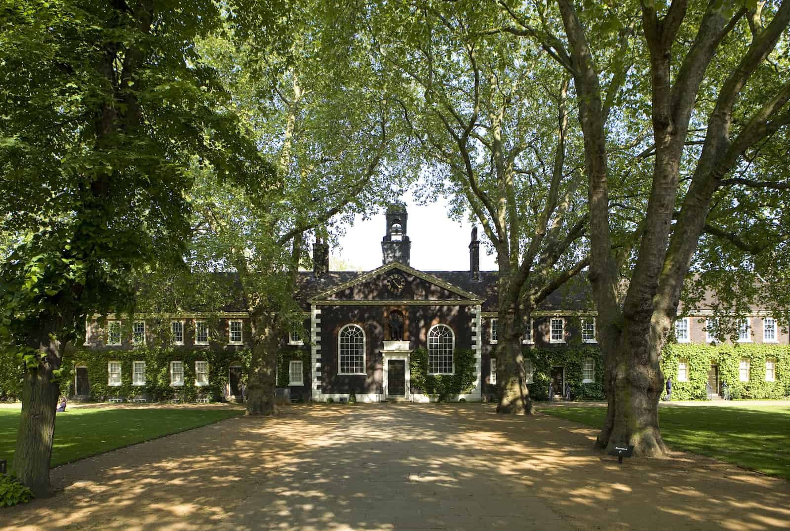 A wide-angle shot of the Museum of the Home Geffrye almshouses in the sunshine. The view is down the central path towards the exterior of the Chapel.