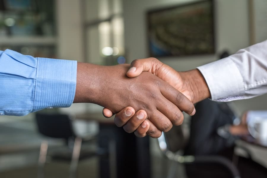 two people shaking hands - trust is essential in a remote work setup Hiring after covid