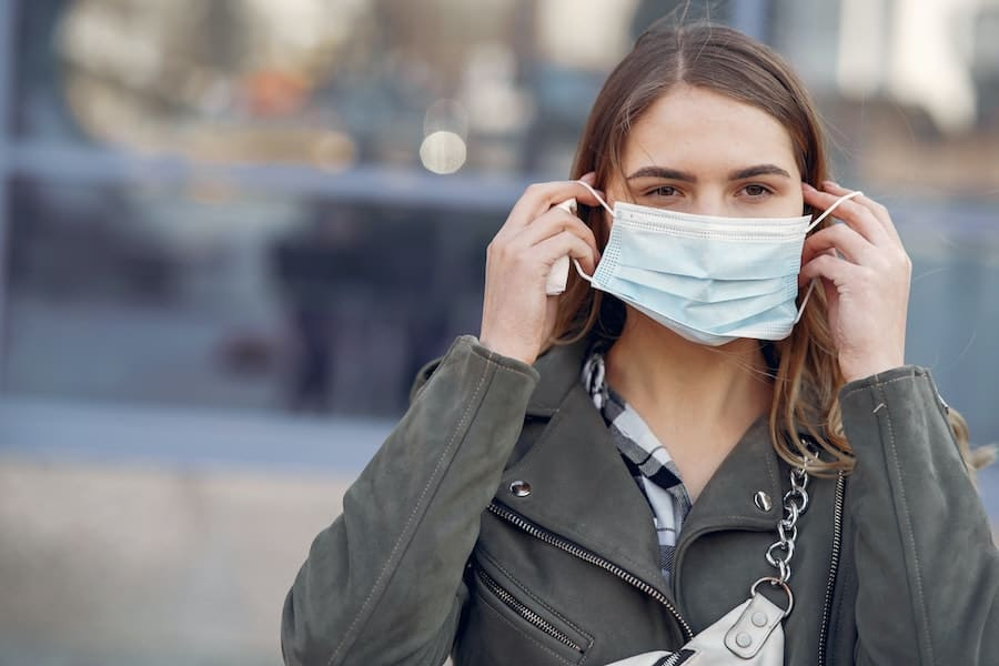 woman in face mask - will masks become the norm as coronavirus impacts the attractions industry in the future