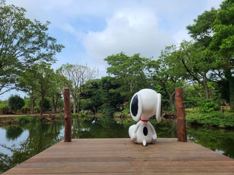 Snoopy statue sitting at edge of lake