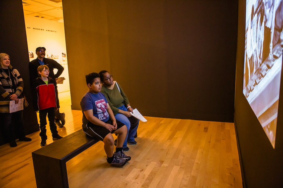 Families watch a video at Philbrook Museum