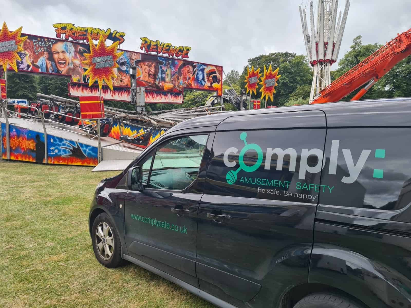 Black van with comply logo on side at theme park