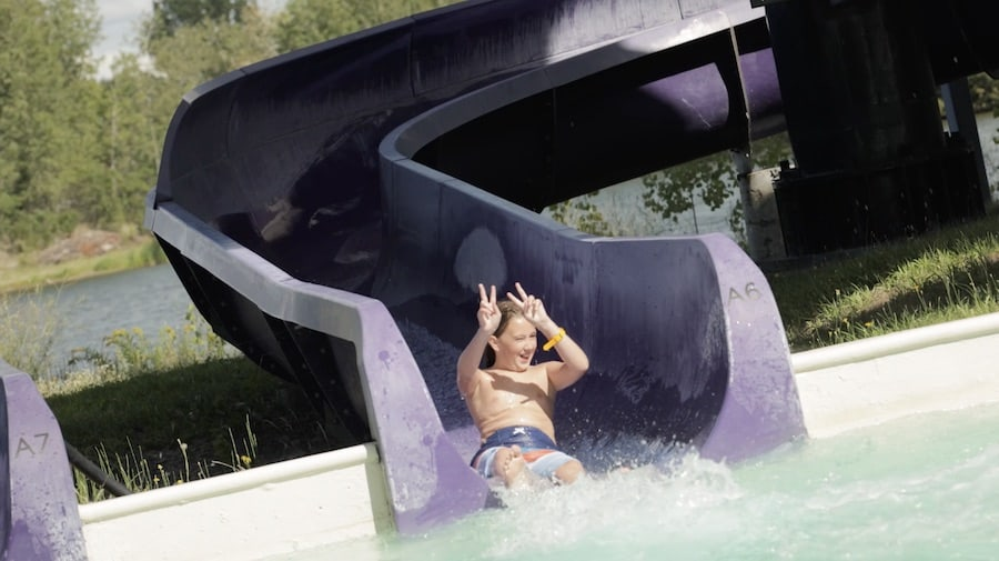 child enjoying waterslide while wearing RFID wristband by Connect&GO