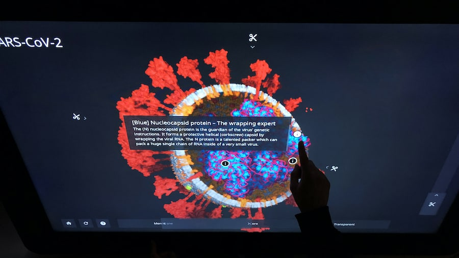 Interspectral corona exhibit finger interacting with a sarscov2 3d model on a touch table