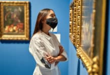 Woman visitor wearing an antivirus mask in the historical museum looking at pictures.