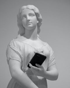 statue holding mobile phone museum