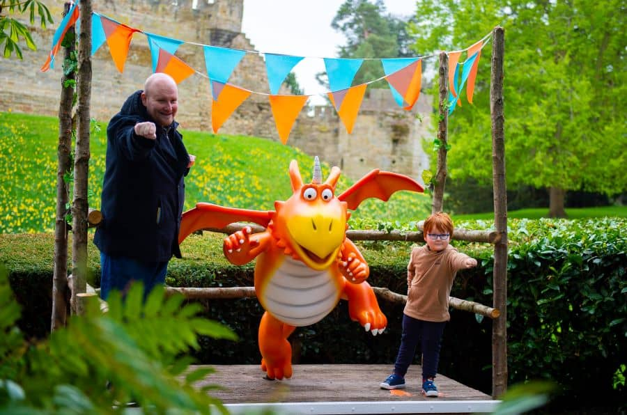 Children poses next to a Zog dragon statue at Warwick Castle